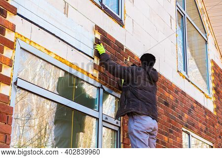 A Man Works With A Drill, Attaches Thermal Panels Made Of Clinker To The Facade Of The House. Clinke