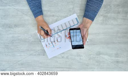 Trader Man Checking Financial Profits On Paper And Smart Phone. Paperwork And Financial Success Conc