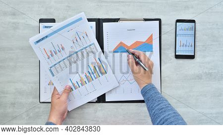 Top View Of  Businessman Hands Counting Profit And Losses And Analyzing Financial Results. Finance A