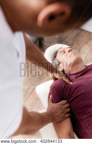Blurred African American Chiropractor Massaging Arm Of Middle Aged Man On Massage Table