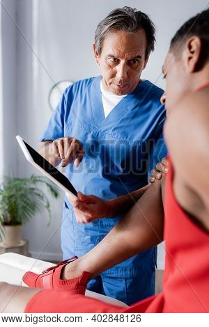 Chiropractor Pointing With Finger At Digital Tablet Near African American Man In Sportswear On Blurr