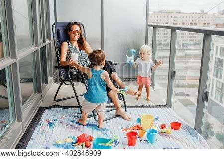 Young Mother Spending Time Together With Children Babies On Balcony At Home. Staycation During Coron