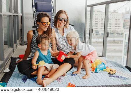 Young Mothers Spending Time Together With Children Babies On Balcony At Home. Lgbtq Female Parents P