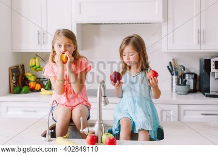 Caucasian Children Girls Eating Fresh Fruits Sitting In Kitchen Sink. Happy Family Sisters Siblings