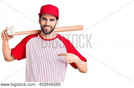 Young handsome man with beard playing baseball holding bat and ball pointing finger to one self smiling happy and proud