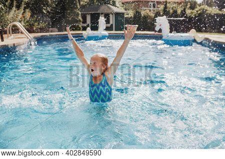 Cute Adorable Girl Swimming In Pool On Home Backyard. Kid Child Enjoying Having Fun In Swimming Pool