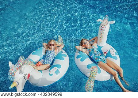 Cute Adorable Girls Sisters Friends With Drinks Lying On Inflatable Rings Unicorns. Kids Children Si