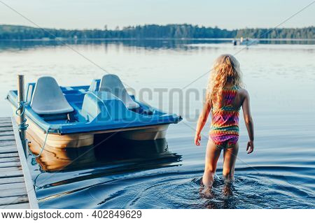 Cute Blonde Girl Walking To Pedal Boat In Lake Water On Sunset. Summer Sport Water Outdoor Activity.