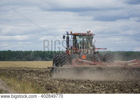 Red Tractor In A Field Rear View, Tractor With A Plow On An Agricultural Field. Big Red Tractor Work