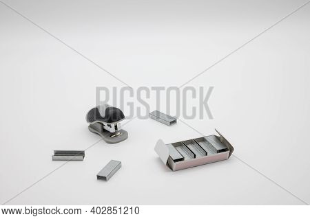 Small Stapler With A Stock Of Staples On A White Background