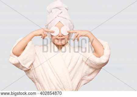 Smiling Beautiful Kid Girl With Towel On Head Hold Cotton Pad Disk Cleansing Face Skin With Cleanser