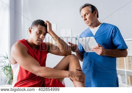 Chiropractor Holding Digital Tablet Near Upset African American Man In Sportswear In Clinic