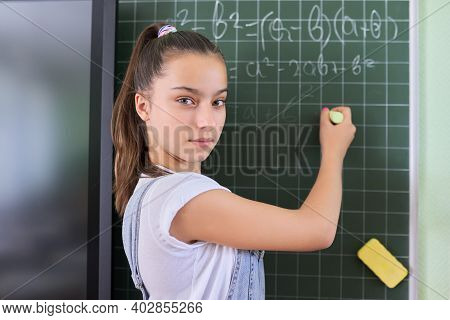 Portrait Of Girl Student Of Teenager 13 Years Old At School Near Chalk Board. Schoolgirl In Classroo