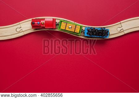 Toy Train With Curved Wooden Railways On Red Background. Wooden Locomotive. Toy Wooden Train Move On