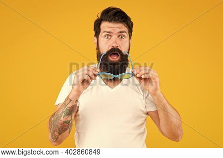 Surprise Party. Surprised Hipster Hold Glasses Yellow Background. Bearded Man Show Surprise On Unsha