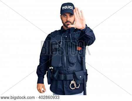 Young hispanic man wearing police uniform doing stop sing with palm of the hand. warning expression with negative and serious gesture on the face.