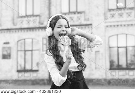 I Am A Star. Girl In Headphones. Little Girl In Classy Uniform Eat Lollipop. Back To School. Modern