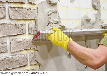Plasterer In Yellow Protective Gloves Spreading Plaster On Wall. Texture Of  Brick Made Of Cement Pl
