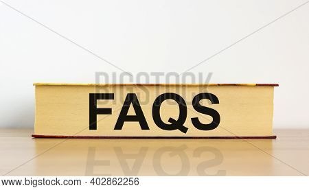Faqs, Frequently Asked Questions Symbol. Book With Word 'faqs, Frequently Asked Questions' On Beauti