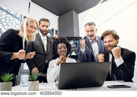 Successful Team Of Multiethnic Business People Are Raising Hands In Fists And Screaming With Happine