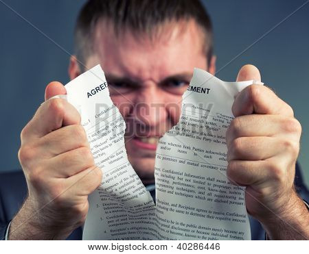 Angry businessman tearing agreement in pieces