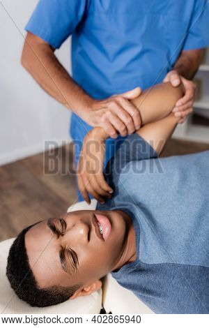 Chiropractor Working With Arm Of Injured African American Patient On Massage Table