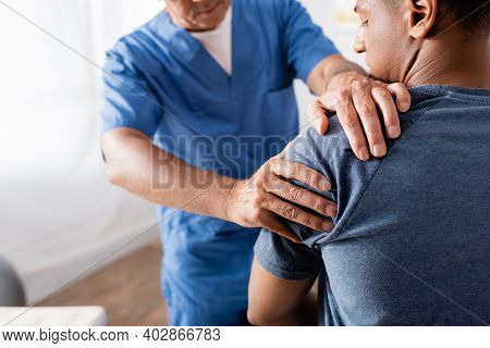 Chiropractor Working With Injured Arm Of African American Patient On Blurred Foreground