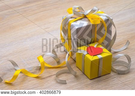 decor for valentine\'s day february 14, gray gift with yellow ribbon, birthday gift, congratulate on the holiday, give a gift,  yellow-gray color in gifts, gift packaging with hearts, valentine\'s day