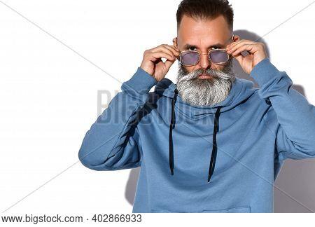Headshot Of Serious Mature Grey-haired Bearded Man In Casual Sweatshirt Touching Trendy Sunglasses O