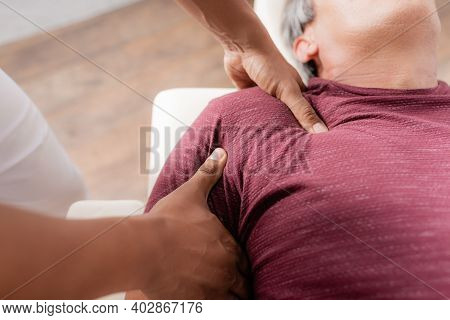 Cropped View Of African American Chiropractor Massaging Arm Of Mature Man On Massage Table