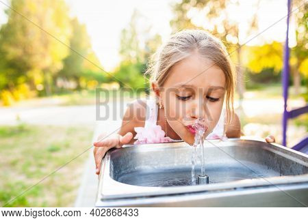 Cheerful Wonderful Girl Drinks Cool Fresh Water From A Small Fountain In A Summer Warm Sunny Park On