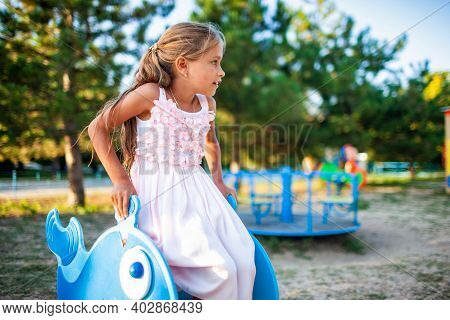 A Lovely Beautiful Little Girl In A Wonderful Pink Delicate Long Dress Sits On A Small Swing In A Wa