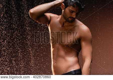 Shirtless Man With Muscular Torso Posing With Hand On Head Under Rain On Dark Background