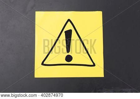 Warning Dangerous Sign Symbol Drawn On Yellow Paper Against Dark Background