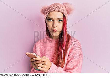 Young caucasian woman having conversation talking on the smartphone puffing cheeks with funny face. mouth inflated with air, catching air.