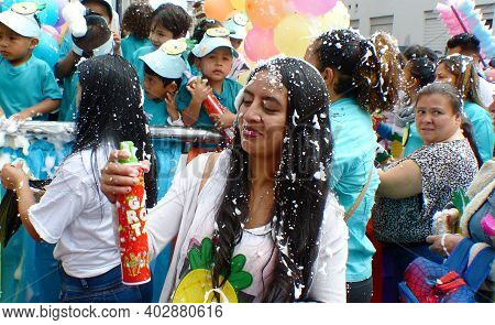 Cuenca, Ecuador - February 22, 2020: Carnival Parade In Cuenca City. Woman With Can Spraying Foam At
