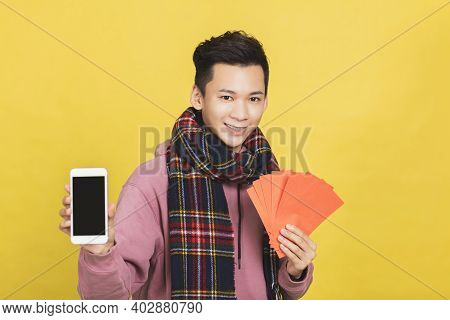 Asian Man Showing Red Envelpoe And Mobile Phone Screen,  Celebrating Chinese New Year Concept