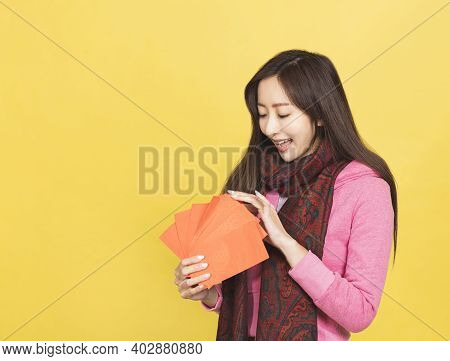Young Asian Woman Looking And Checking The Red Envelope For Celebrating Chinese New Year