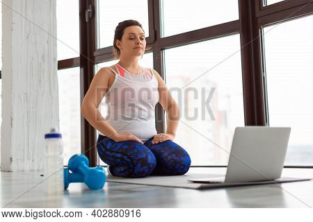 Middle Aged Woman Meditating. She Sits On Her Knees In Front Of The Monitor. Healthy Lifestyle Conce