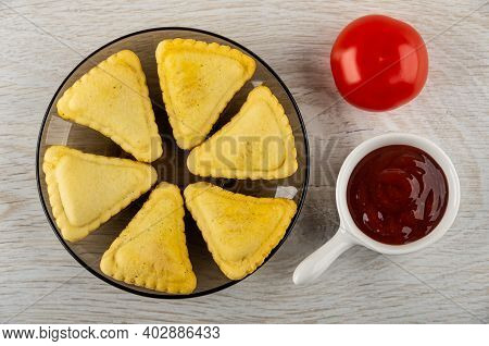 Few Small Savory Pies In Glass Brown Saucer, Red Tomato, Sauce Boat With Ketchup On Wooden Table. To
