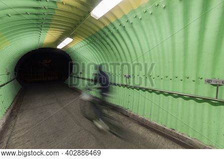 Biker Riding On Bicycle In Modern Tunnel