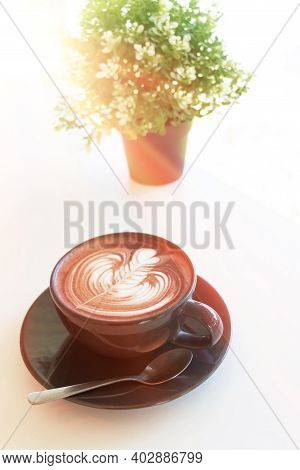 Hot Organic Cocoa With Foam Froth Art In Black Ceramic Cup On White Table In Cafe