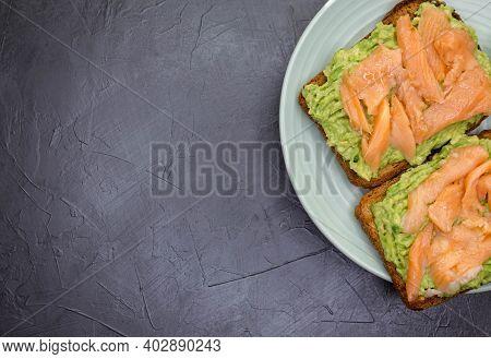 Crisp Sandwiches With Avocado And Salmon. Closeup Of Toast With Dark Rye Bread, Guacamole, Smoked Sa