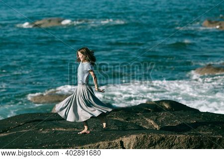 Young woman is engaged in choreography on the ocean coast.
