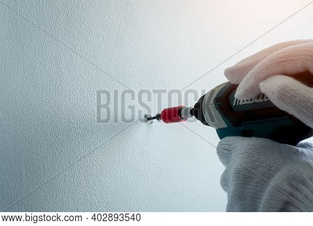 People Hand Drilling Screw Into Apartment Wall With Cordless Drill. People Wear White Gloves And Han