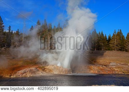 Eruption of Riverside Geyser on Firehole river in Yellowstone National Park, Wyoming, USA. Beautiful american landscapes