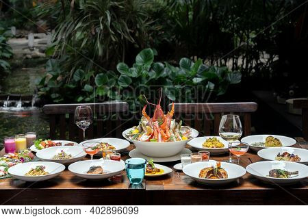 Side view premium variety of international food in garden of restaurant of lobster shrimp steak beef lamb pasta spaghetti risotto rice sushi sashimi and wine using for buffet food drink background.