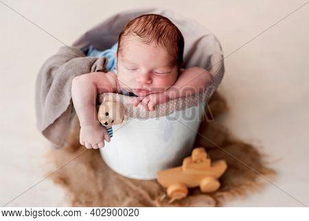 Newborn sleeping in cradle holding toy