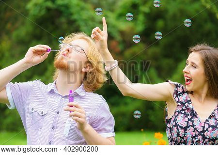 Happiness And Carefree Concept. Young Woman And Man Having Fun Blowing Soap Bubbles Together In Park