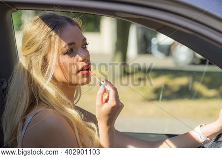Young Attractive Woman Looking In Rear View Mirror Painting Her Lips Applying Lipstick Lip Gloss Mak